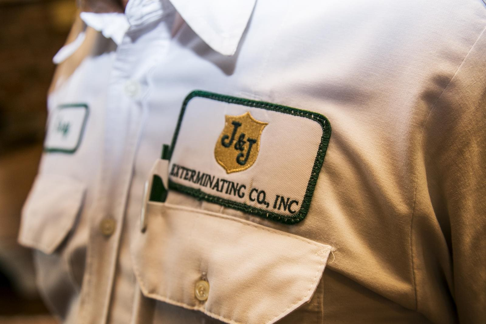 J&J Exterminating badge on pest control operator's shirt